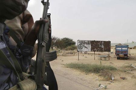 Chadian soldiers drive past a signpost painted by Boko Haram in the recently retaken town of Damasak