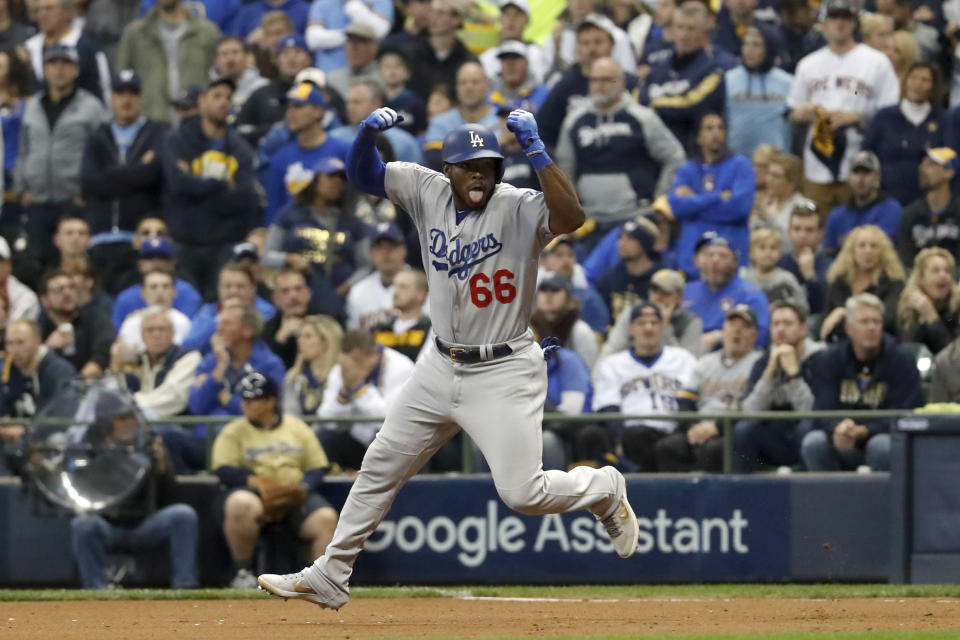 Yasiel Puig celebrates as he runs the bases after hitting a three-run home run during the sixth inning in NLCS Game 7. (AP)