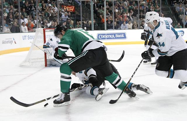 Dallas Stars' Alex Chiasson (12) competes with San Jose Sharks defenseman Justin Braun, bottom, for control of a loose puck as the Sharks' Marc-Edouard Vlasic (44) assist on the play in the first period of an NHL hockey game, Thursday, Oct. 17, 2013, in Dallas. (AP Photo/Tony Gutierrez)