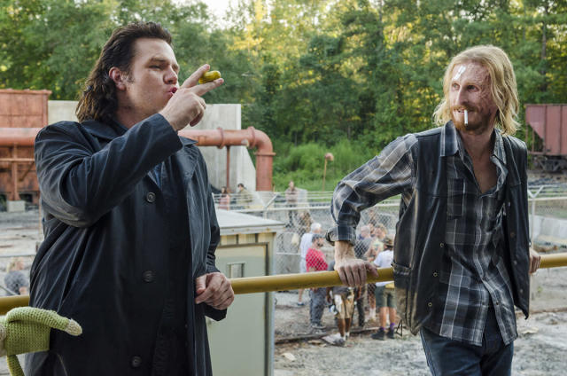 <p>Dwight portrayer Austin Amelio lights up a cigarette as Josh McDermitt pretends to smoke his Eugene's favorite snack, a pickle.<br><br>(Photo: AMC) </p>