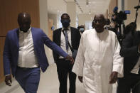 FILE - In this June 10, 2020 file photo, former president of the IAAF (International Association of Athletics Federations) Lamine Diack, right, arrives at the Paris courthouse. A Paris court is delivering its verdict Wednesday Sept. 16, 2020, in the trial of Lamine Diack on corruption, money laundering and breach of trust charges against the one-time supremo of global track and field athletics, and according to prosecutors, creamed off millions for himself, with his son. (AP Photo/Thibault Camus, File)