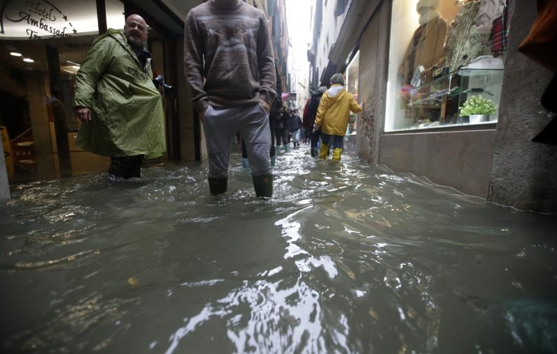 People wade through water on the occasion of a high tide, in a flooded Venice, Italy, Tuesday, Nov. 12, 2019. (Photo: Luca Bruno/AP)