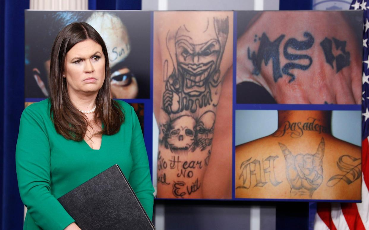 White House press secretary Sarah Huckabee Sanders stands in front of pictures of MS-13 gang tattoos during a press briefing at the White House in Washington, Thursday, July 27, 2017 - AP