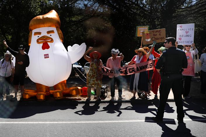 Demonstrators stand beside an inflatable chicken mocking President Trump as the presidential motorcade passes by in Palo Alto, Calif. (Photo: Tom Brenner/Reuters)