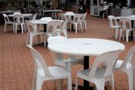 Stall owner waits for customers at a largely empty food court in Singapore