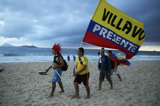 Colombian soccer fans carry a flag as they walk on Ipanema beach ahead the 2014 World Cup in Rio de Janeiro, June 11, 2014 REUTERS/Pilar Olivares (BRAZIL - Tags: SOCCER SPORT WORLD CUP ENVIRONMENT SOCIETY)