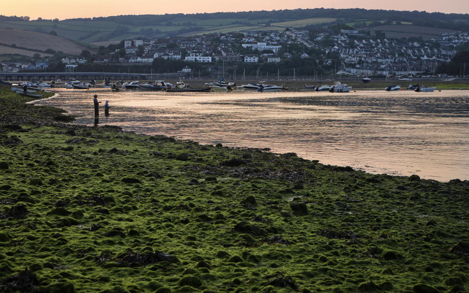 People fish in the Teign estuary in Shaldon, Devon, England as the sun sets on Tuesday July 20, 2021. (AP Photo/Tony Hicks)
