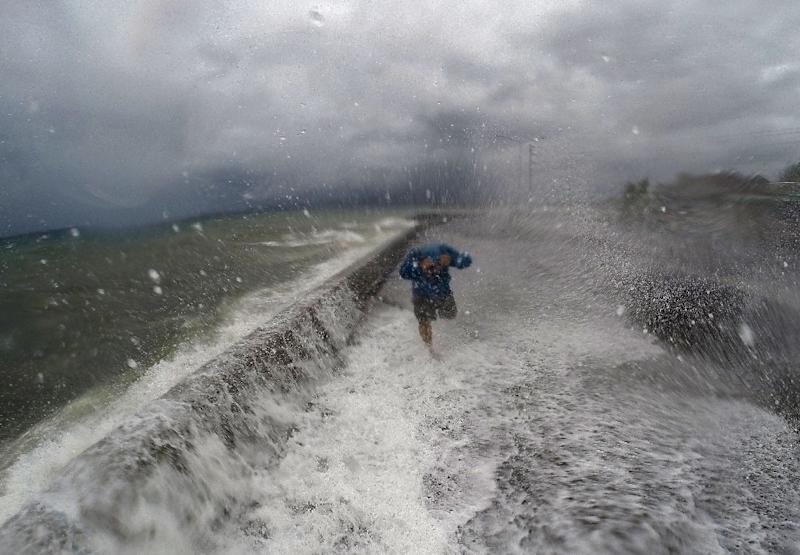 Waves spill over a wall onto a road in Legaspi in Albay province south of Manila on December 14, 2015 (AFP Photo/Charism Sayat)