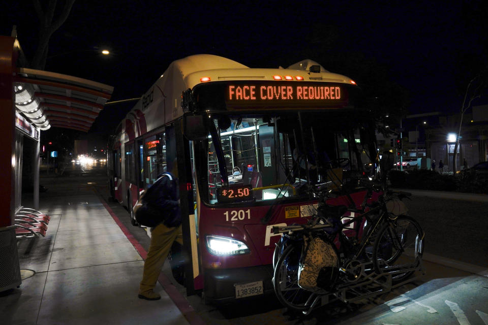 """A man wears a mask to prevent the spread of coronavirus as he boards a city bus Tuesday, Nov. 24, 2020, in San Diego. California's health secretary urged people to say """"no"""" to family and friends who want to gather for Thanksgiving, joining other officials in issuing dire warnings about the spread of the coronavirus. (AP Photo/Gregory Bull)"""