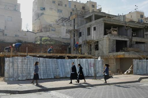 Ultra-orthodox Jews walk in the Israeli settlement of Beitar Illit as Palestinian labourers work at a construction site on February 14, 2018