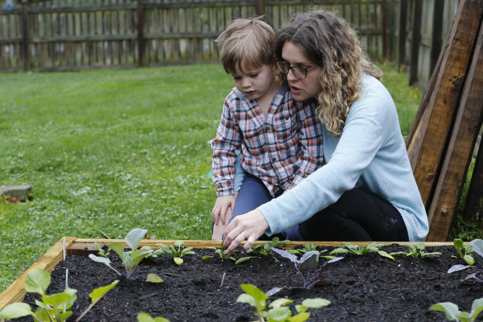 Stephanie Owens looks over the garden with her son, Cole, as they tend to it at their home Wednesday March 25 , 2020, in Glen Allen, Va. Owens is a pharmacist who has had to continue to go to work, but has been able to spend more time with her kids because they are home from school . One of the activities that they have done is planting the garden. (AP Photo/Steve Helber)