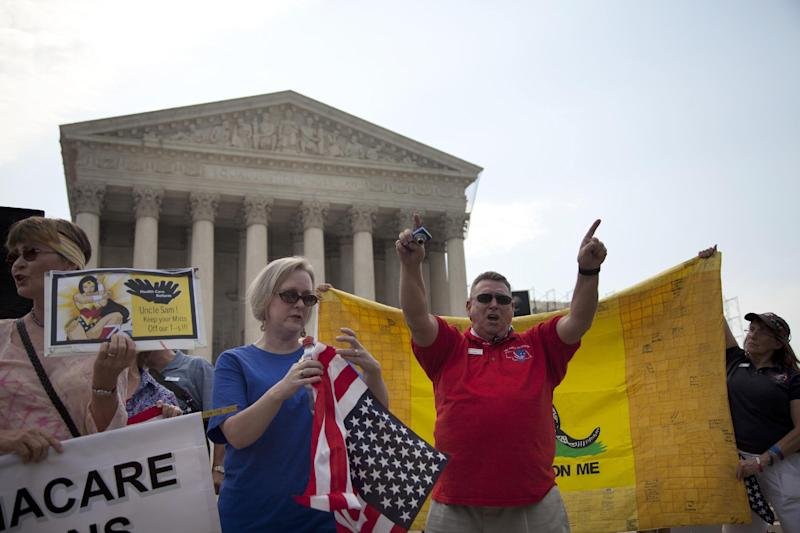 Demonstrators stand outside the Supreme Court in Washington, Monday, June 25, 2012. The Supreme Court is meeting Monday to issue opinions in some of the handful of cases that remain unresolved. (AP Photo/Evan Vucci)