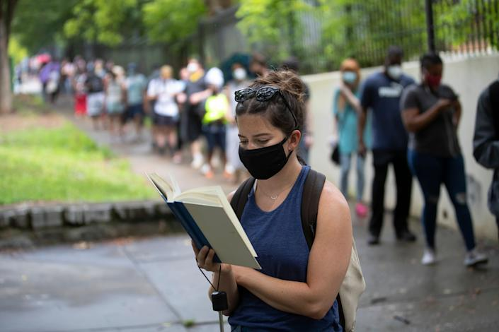 Kelsey Luker reads as she waits in line to vote on June 9 in Atlanta. Luker said she had been in line for almost two hours. Voters reported wait times of three hours. (Photo: ASSOCIATED PRESS/John Bazemore)