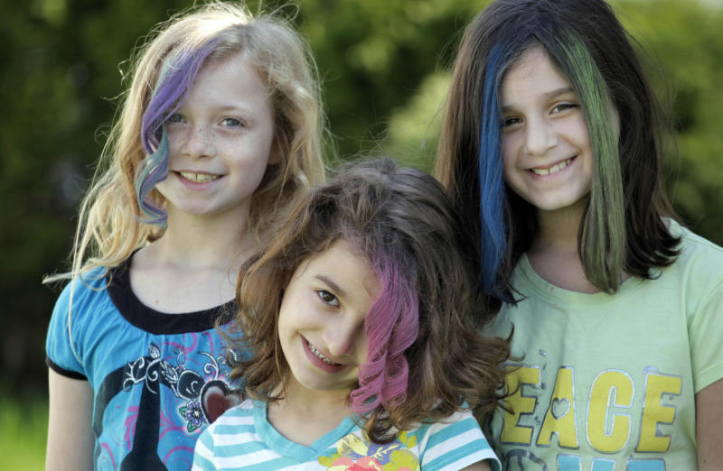 In this photo taken, Monday, April 2, 2012, Maddie Parizek, Sadie Moussa, and Gabriella Lujan, left to right, show off their hairstyles created with soft pastel chalk applied by neighborhood mom Orly Telisman in Chicago. Everyone from hipsters to children to Hollywood celebrities is embracing the runway fad for brightly colored hair, using soft pastel chalk.  (AP Photo/M. Spencer Green)
