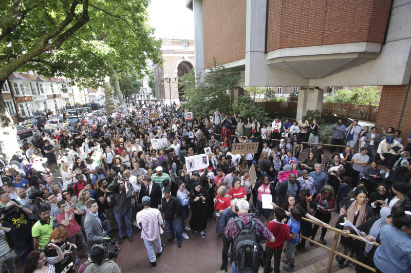Protesters gather outside Kensington town hall in west London, the headquarters of the Royal Borough of Kensington and Chelsea, demanding answers over the Grenfell Tower fire disaster, Friday June 16, 2017. Grief over a London high-rise tower fire that killed dozens turned to outrage Friday amid reports that the materials used in a recent renovation of the public housing block may have fueled the inferno. (Yui Mok/PA via AP)