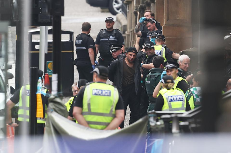 A man is led away by police officers at the scene in West George Street, Glasgow. (PA)