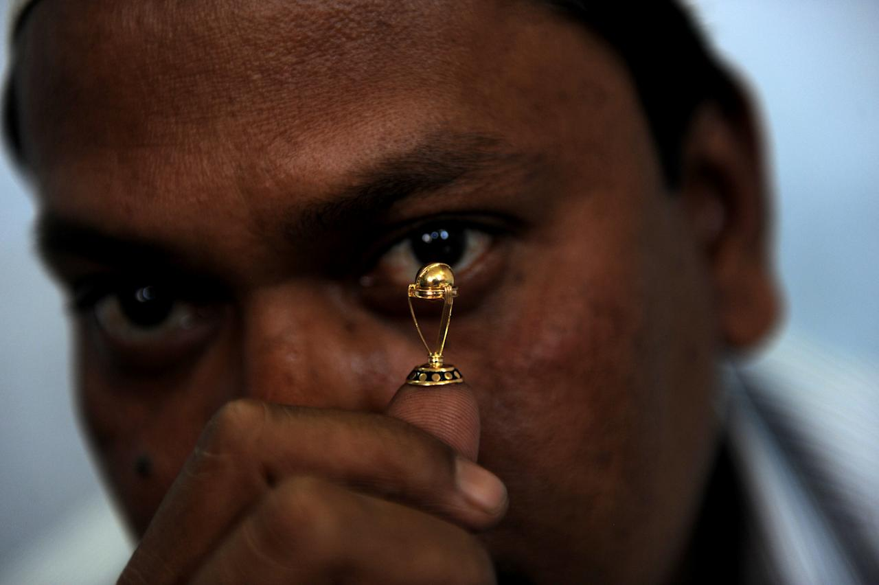 Indian jeweller Shaikh Abdul Rauf displays his creations of a replica miniature Cricket World Cup trophy made of 21 Carat gold in Ahmedabad on March 22, 2011. Rauf and fellow jeweller Soni Sukumar Mathur in the western Indian city each made a replica minature in eight days and want to present them to Indian cricket captain Mahendra Singh Dhoni if he leads his team to victory in the continuing tournament which has reached it's quarter-final stages. AFP PHOTO/Sam PANTHAKY (Photo credit should read SAM PANTHAKY/AFP/Getty Images)