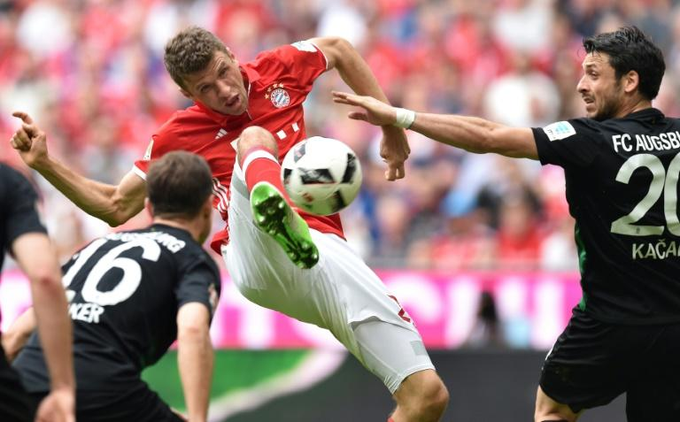 Bayern Munich's Thomas Mueller (C) controls the ball under pressure from Augsburg players in Munich, southern Germany, on April 1, 2017