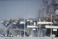 Fire crews spray water from the dock onto the side of the USS Bonhomme Richard, Tuesday, July 14, 2020, in San Diego. The battle to save the ship from a ravaging fire entered a third day in San Diego Bay on Tuesday with indications that the situation aboard the amphibious assault ship was improving. The U.S. Navy said in a statement late Monday that firefighters were making significant progress with the assistance of water drops by helicopters. (AP Photo/Gregory Bull)