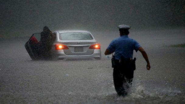 PHOTO: A police officer rushes to help a stranded motorist during Tropical Storm Isaias, Aug. 4, 2020, in Philadelphia. (Matt Slocum/AP)
