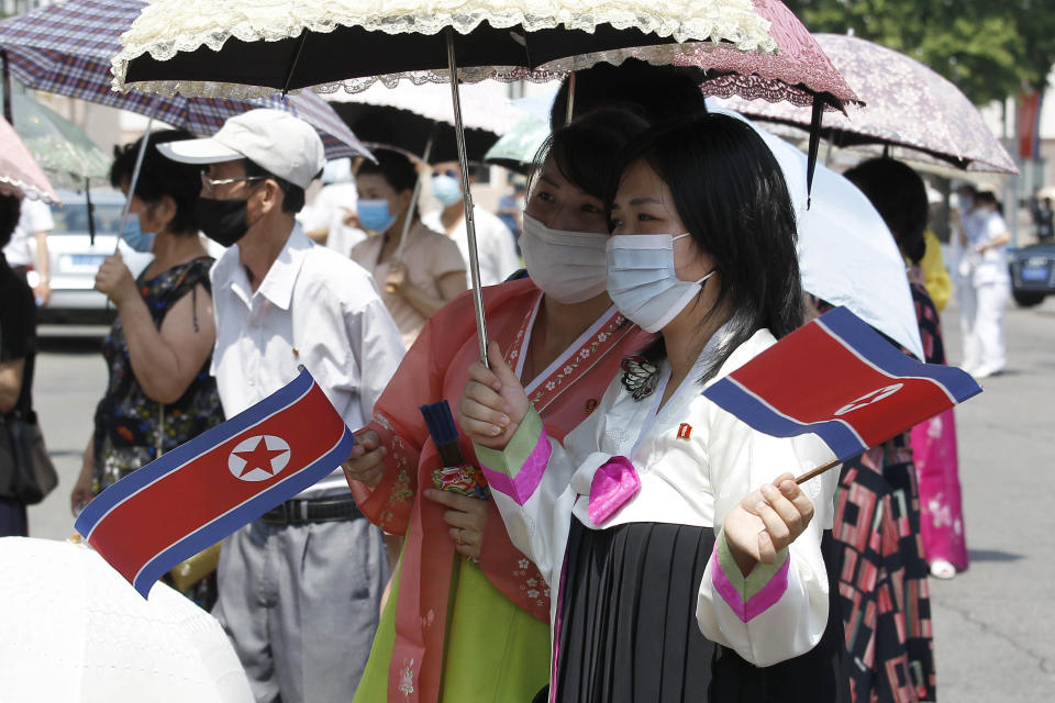 Pyongyang citizens holding North Korean flags watch a performance by an art troupe in front of the Pyongyang Grand Theatre in Pyongyang, North Korea, Tuesday, July 27, 2021, to mark the Korean War armistice anniversary. The leaders of North and South Korea restored suspended communication channels between them and agreed to improve ties, both governments said Tuesday, amid a 2 ½ year-stalemate in U.S.-led diplomacy aimed at stripping North Korea of its nuclear weapons. (AP Photo/Cha Song Ho)