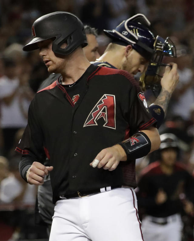 Arizona Diamondbacks' Carson Kelly scores on a double hit by Zach Greinke as Milwaukee Brewers catcher Yasmani Grandal looks down during the fifth inning of a baseball game, Saturday, July 20, 2019, in Phoenix. (AP Photo/Matt York)