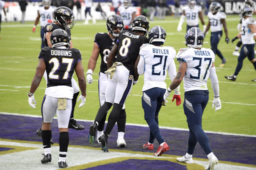 Baltimore Ravens quarterback Lamar Jackson (8) bumps Tennessee Titans cornerback Malcolm Butler (21) as the Ravens celebrate a touchdown catch by Mark Andrews, center left, during the second half of an NFL football game, Sunday, Nov. 22, 2020, in Baltimore. (AP Photo/Nick Wass)