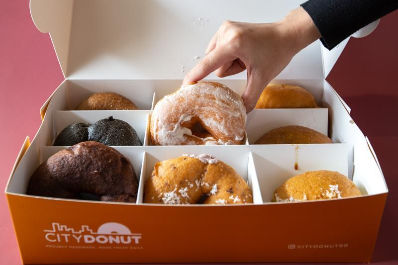 Hand reaching for doughnuts from City Donut box