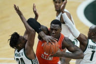 Illinois center Kofi Cockburn (21) is defended by Michigan State forward Julius Marble II (34) and guard Joshua Langford (1) during the first half of an NCAA college basketball game, Tuesday, Feb. 23, 2021, in East Lansing, Mich. (AP Photo/Carlos Osorio)