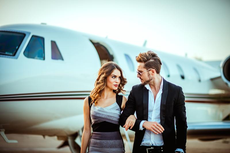 Rich and famous couple walking together with hands crossed. They are walking away from a private jet parked on a tarmac.