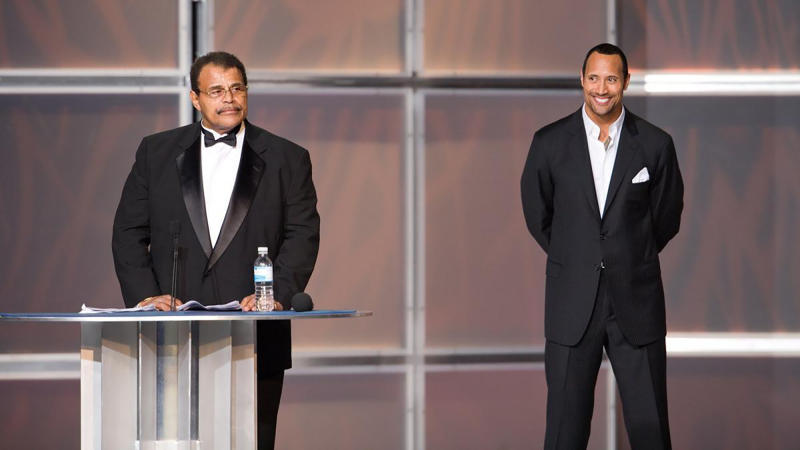 """In this 2008 photo provided by WWE, Inc., Rocky """"Soul Man"""" Johnson, left, speaks at his WWE Hall of Fame induction ceremony, as his son, Dwayne """"The Rock"""" Johnson watches. Rocky Johnson died Wednesday, Jan. 15, 2020. He was 75. (WWE, Inc. via AP)"""