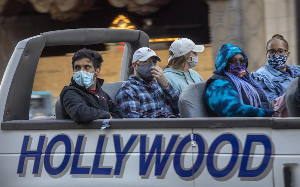 People wear masks on an open-top tour bus with the word Hollywood on the side