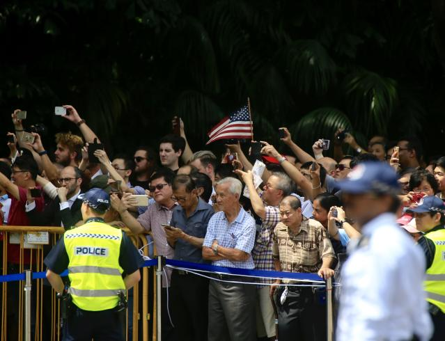 <p>People wave as the convoy of President Trump will meet with North Korean leader Kim Jong-un on June 12 in Singapore. (Photo: VCG/VCG via Getty Images) </p>