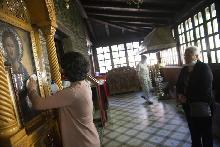 In this Sunday, May 24, 2020, photo, a woman cleans an icon with disinfectant as the faithful wait to kiss it inside a Greek Orthodox church the northern city of Thessaloniki, Greece. Priests at the church still use a traditional shared spoon to distribute Holy Communion. Contrary to science, the Greek Orthodox Church says it is impossible for any disease, including the coronavirus, to be transmitted through Holy Communion. (AP Photo/Giannis Papanikos)