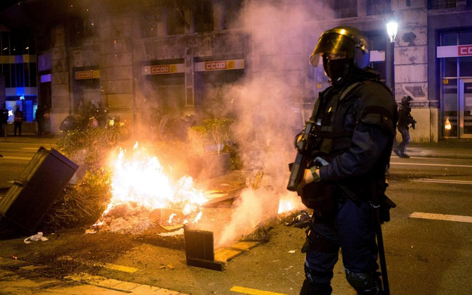Mossos d'Esquadra agents stand guard as COVID-19 deniers burn urban furniture during a march to protest - Shutterstock