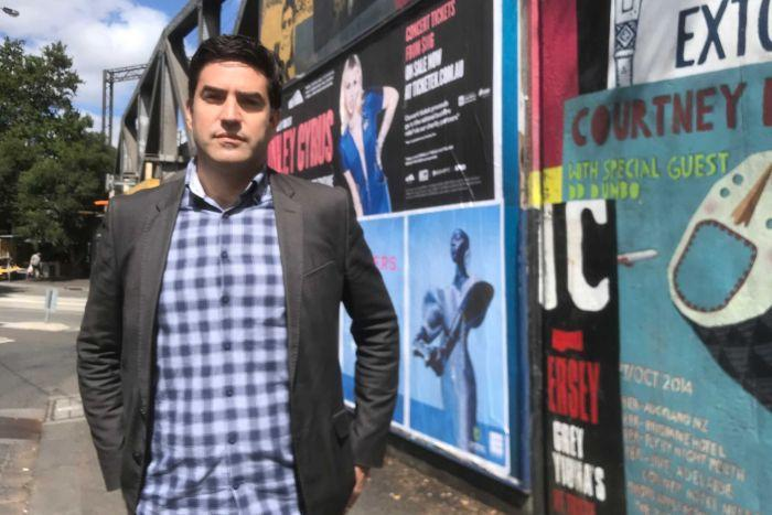 Adam Portelli stands on the street, in front of a number of promotional posters for gigs.