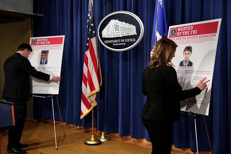 Department of Justice staffers install posters of a suspected Russian hacker before FBI National Security Division and the U.S. Attorney's Office for the Northern District of California joint news conference at the Justice Department in Washington, U.S., March 15, 2017. REUTERS/Yuri Gripas