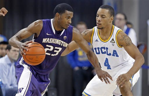Washington guard C.J. Wilcox (23) drives as UCLA guard Norman Powell (4) defends during the second half of an NCAA college basketball game in Los Angeles on Thursday, Feb. 7, 2013. Wilcox had a team-high 15 points as UCLA won 59-57. (AP Photo/Reed Saxon)