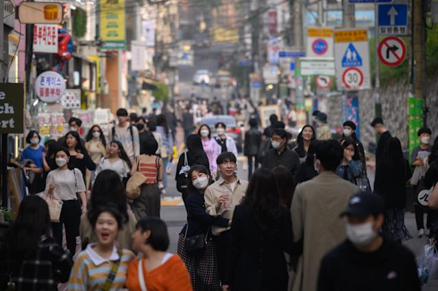 People wearing face masks walk along a street in the Hongdae district of Seoul. (Getty)