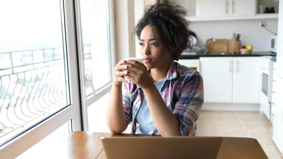 Woman drinking coffee and using laptop at home.