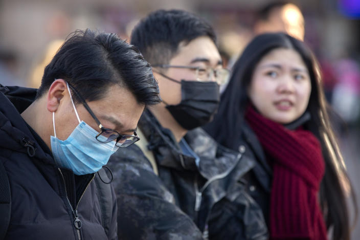 Travelers wear face masks as they walk outside of the Beijing Railway Station in Beijing after China reported a sharp rise in the number of people infected with a new coronavirus. (AP)