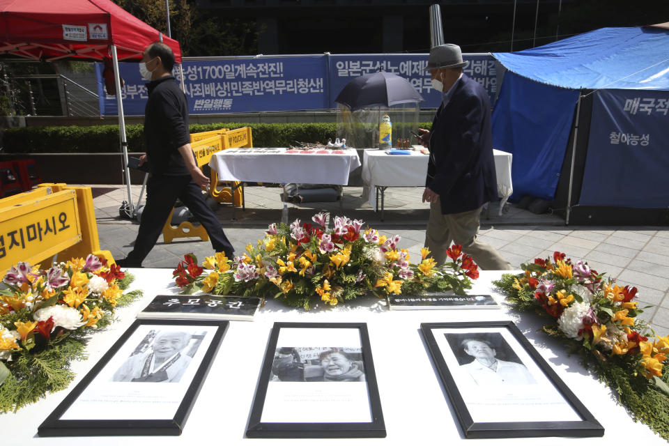 Portraits of the late former South Korean comfort women are displayed near Japanese Embassy in Seoul, South Korea, Wednesday, April 21, 2021. A South Korean court on Wednesday rejected a claim by South Korean sexual slavery victims and their relatives who sought compensation from the Japanese government over their wartime sufferings. (AP Photo/Ahn Young-joon)
