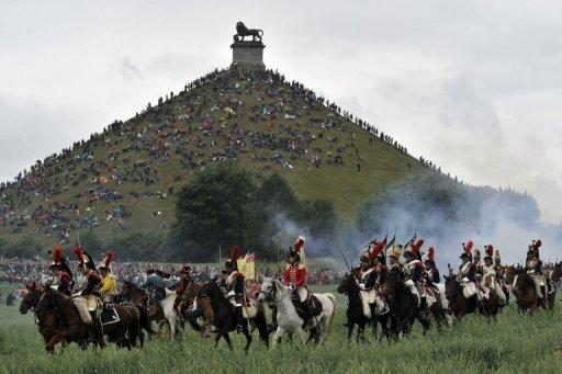 People sit on the Lion's Mound, around the lion monument of the Battle of Waterloo during a re-enactment in 2010