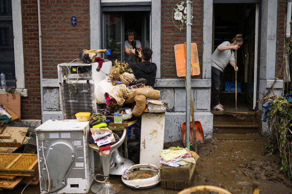 People pass damaged belongings out of a house after flooding in Ensival, Verviers, Belgium, Friday July 16, 2021. Severe flooding in Germany and Belgium has turned streams and streets into raging torrents that have swept away cars and caused houses to collapse. (AP Photo/Francisco Seco)