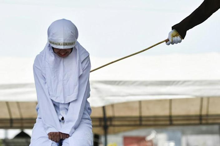 A woman is whipped in public in Banda Aceh in Indonesia's staunchly conservative Aceh province (AFP Photo/CHAIDEER MAHYUDDIN)