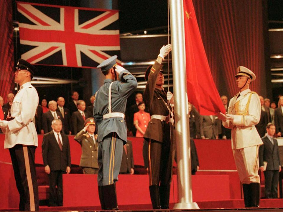 Chinese soldiers raise the countries at the Hong Kong convention centre to mark the moment Hong Kong reverted to Chinese rule in July 1997: AP
