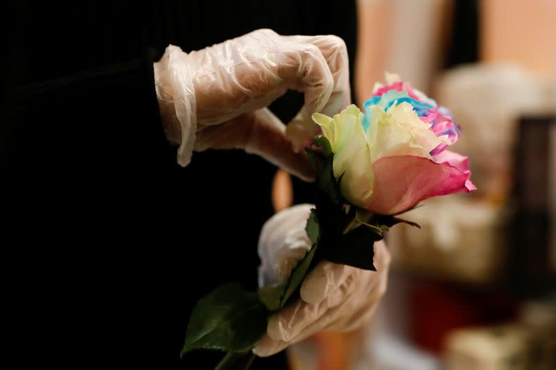 A florist who prefers to be called Cai Xiaoman wearing gloves, holds a rose while she ensembles a bouquet at a flowers shop in a shopping mall, as the country is hit by an outbreak of the new coronavirus, in Beijing