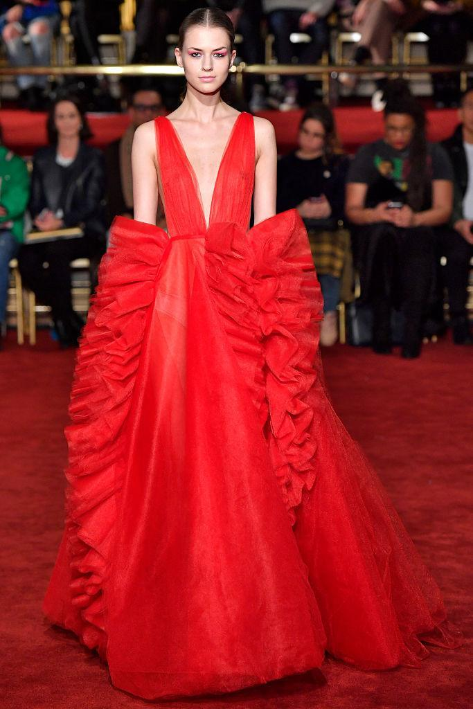 <p>A odel wears a deep-cut red ruffle dress at the Christian Siriano FW18 show. (Photo: Getty) </p>