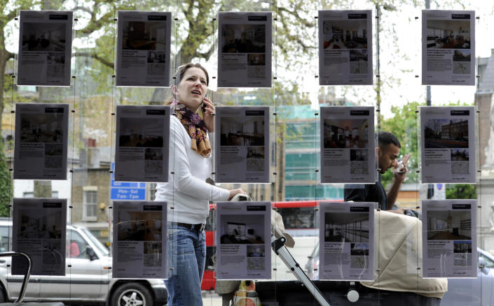 A woman stops to look in the window of an estate agent in Islington, north London. Photo: Paul Hackett/Reuters