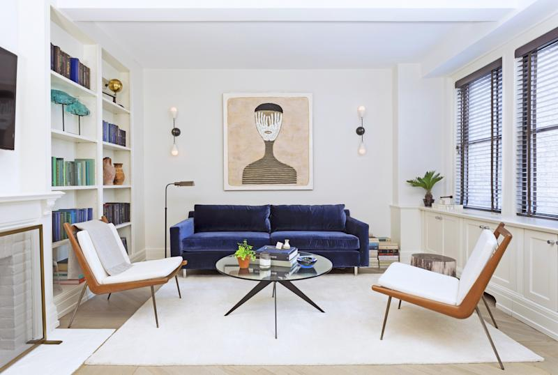 Designer Ashley Darryl put a modern spin on her friend Jeremy Globerson's one-bedroom apartment in Manhattan by using clean-lined furnishings and carefully selected accents. Sconces by Apparatus and a painting by Hector Frank are displayed above the Mitchell Gold + Bob Williams sofa in the living room.